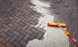 brampton-paving-employee-spreading-sand-with-a-broom