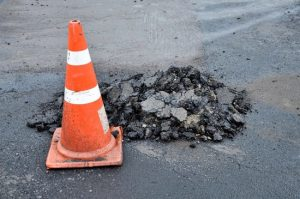 road-cone-with-pothole-on-pavement