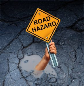 road-hazard-sign-on-road-with-pothole